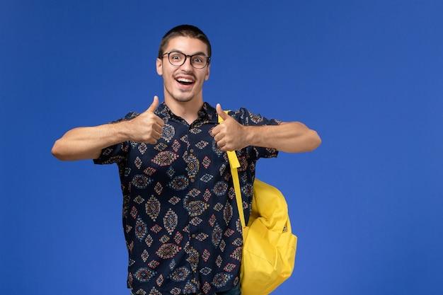 Vooraanzicht van mannelijke student in donker katoenen overhemd die gele rugzak dragen die zich op lichtblauwe muur verheugen