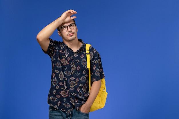 Vooraanzicht van mannelijke student in donker katoenen overhemd die gele rugzak met beklemtoonde uitdrukking op lichtblauwe muur dragen