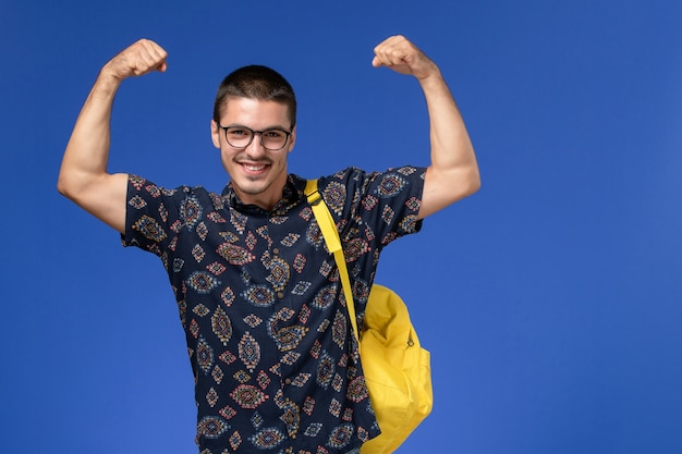 Vooraanzicht van mannelijke student in donker overhemd die gele rugzak draagt die op de blauwe muur buigt