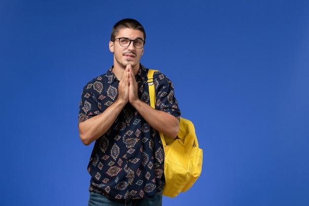 Vooraanzicht van mannelijke student in donker overhemd die gele rugzak dragen die aan de blauwe muur denken