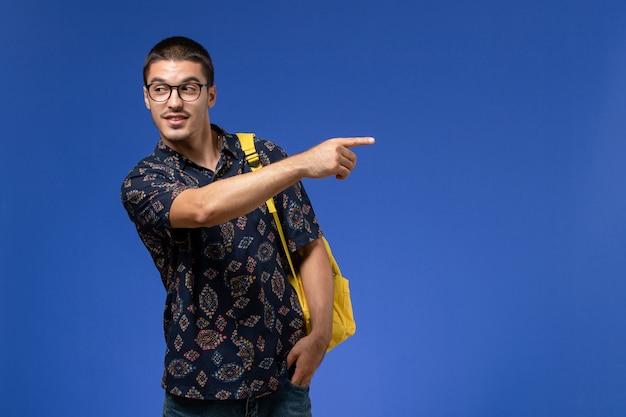 Vooraanzicht van mannelijke student in donker overhemd die gele rugzak dragen die op de blauwe muur wijzen