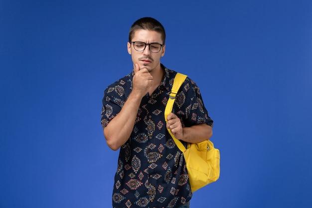 Vooraanzicht van mannelijke student in donker overhemd die gele rugzak dragen die op lichtblauwe muur denken