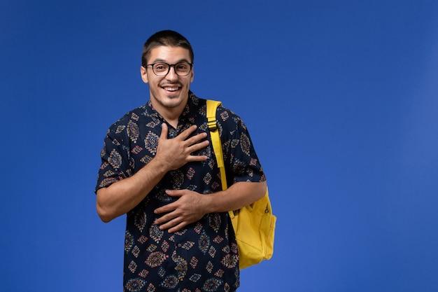 Vooraanzicht van mannelijke student in donker overhemd gele rugzak dragen op de blauwe muur