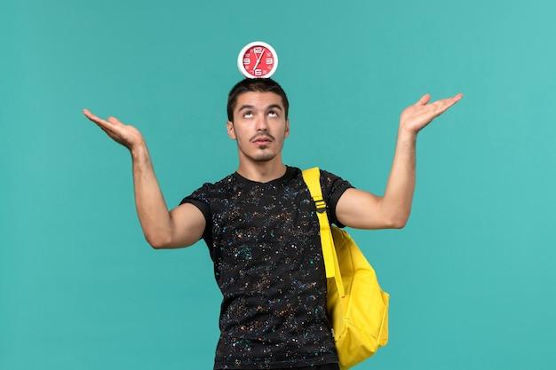 Vooraanzicht van mannelijke student in donkere t-shirt gele rugzak klokken met zijn hoofd op de lichtblauwe muur te houden