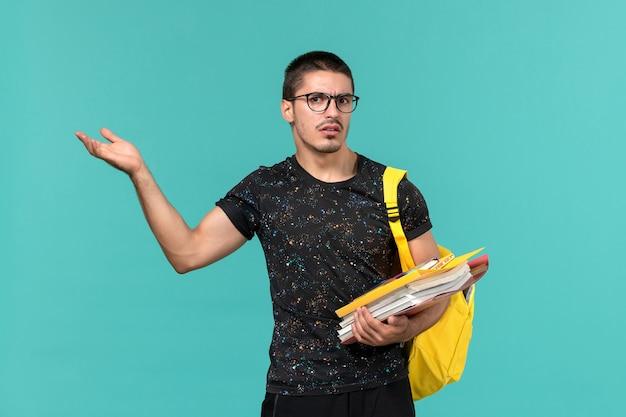 Vooraanzicht van mannelijke student in donkere t-shirt gele rugzak met bestanden en boeken op lichtblauwe muur