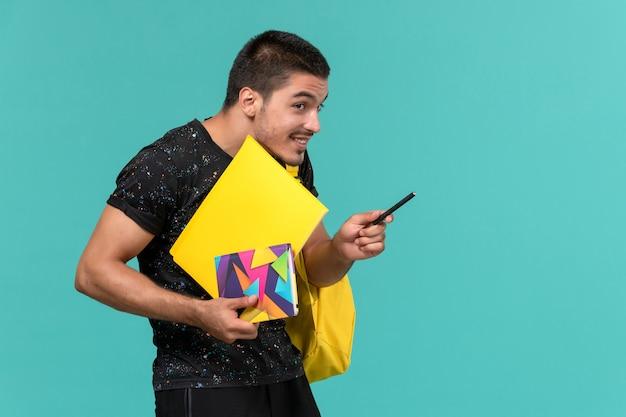 Vooraanzicht van mannelijke student in donkere t-shirt gele rugzak met bestanden en voorbeeldenboek op de lichtblauwe muur