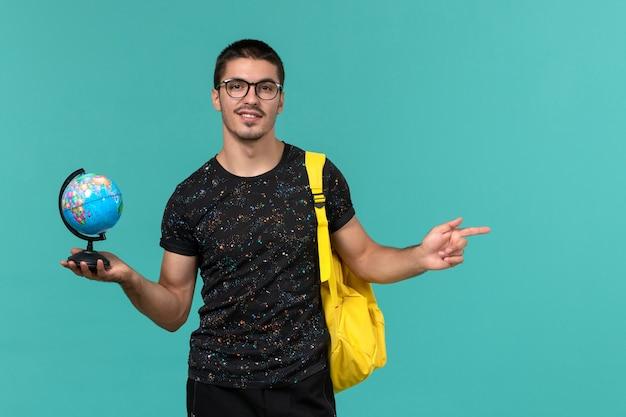 Vooraanzicht van mannelijke student in donkere t-shirt gele rugzak met kleine wereldbol lachend op blauwe muur