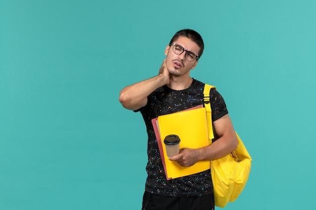 Vooraanzicht van mannelijke student in donkere t-shirt gele rugzak met verschillende bestanden en koffie met nekpijn op blauwe muur