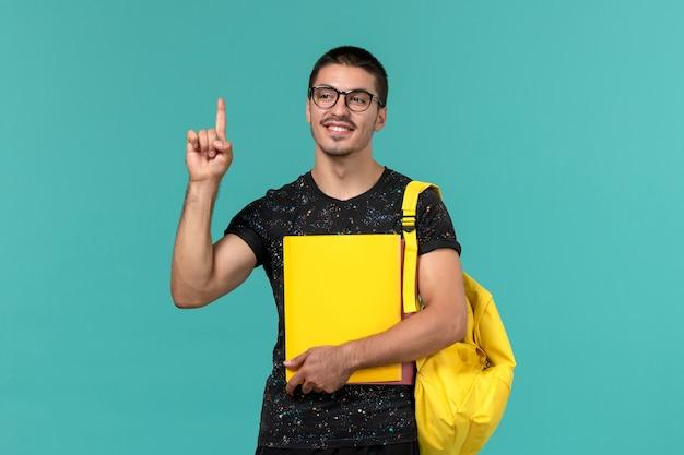 Vooraanzicht van mannelijke student in donkere t-shirt gele rugzak met verschillende bestanden op de lichtblauwe muur