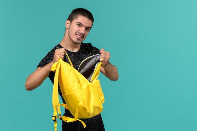 Vooraanzicht van mannelijke student in donkere t-shirt gele rugzak op lichtblauwe muur