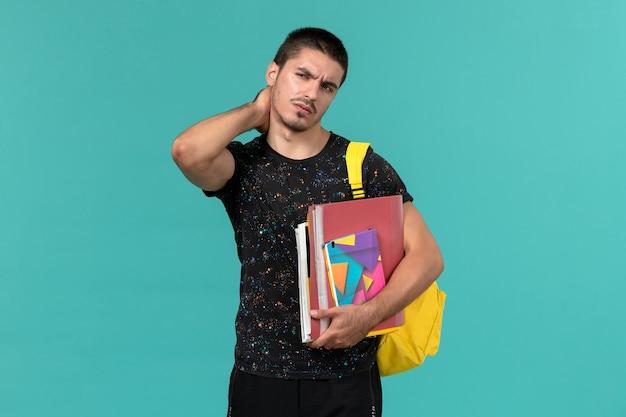 Vooraanzicht van mannelijke student in donkere t-shirt met gele rugzak met voorbeeldenboek en bestanden met nekpijn op blauwe muur