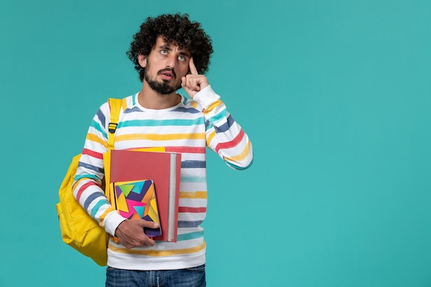 Vooraanzicht van mannelijke student in gekleurd gestreept overhemd die gele rugzak dragen die dossiers en voorbeeldenboeken houden die op blauwe muur denken