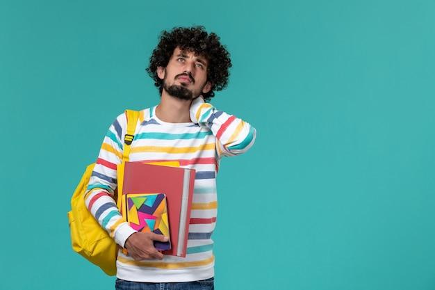 Vooraanzicht van mannelijke student in gekleurd gestreept overhemd met gele rugzak met bestanden en voorbeeldenboeken met nekpijn op blauwe muur