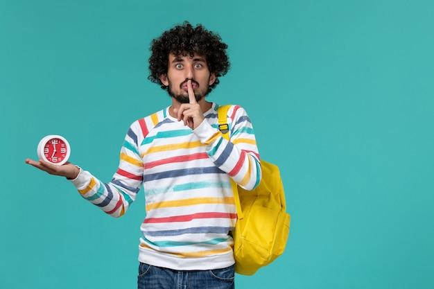 Vooraanzicht van mannelijke student in gestreept overhemd die de gele klokken van de rugzakholding dragen die stilte teken tonen op blauwe muur