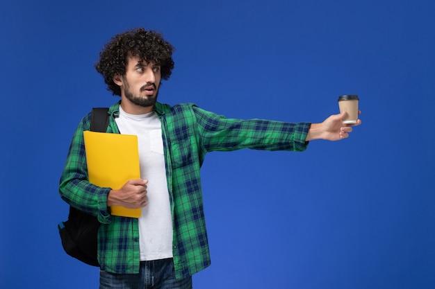 Vooraanzicht van mannelijke student in groen geruit overhemd die zwarte rugzak draagt en dossiers en koffie op de blauwe muur houdt