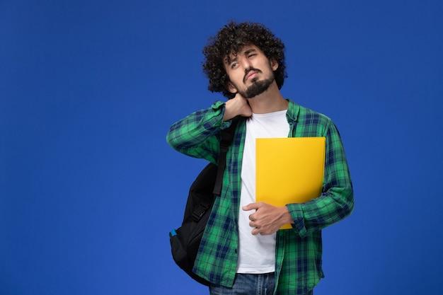 Vooraanzicht van mannelijke student in groen geruit overhemd die zwarte rugzak draagt en dossiers met nekpijn op de blauwe muur houdt