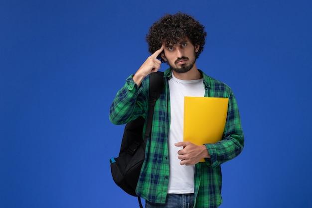 Vooraanzicht van mannelijke student in groen geruit overhemd die zwarte rugzak draagt en dossiers op de blauwe muur houdt