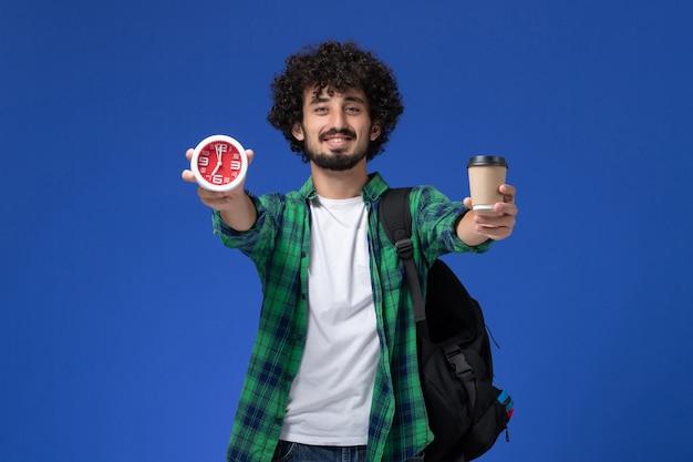 Vooraanzicht van mannelijke student in groen geruit overhemd die zwarte rugzak draagt en klokken en koffie op blauwe muur houdt