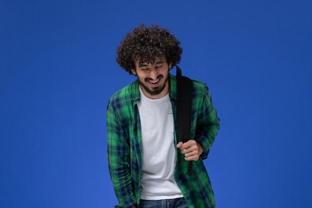 Vooraanzicht van mannelijke student in groen geruit overhemd die zwarte rugzak draagt en op de blauwe muur lacht