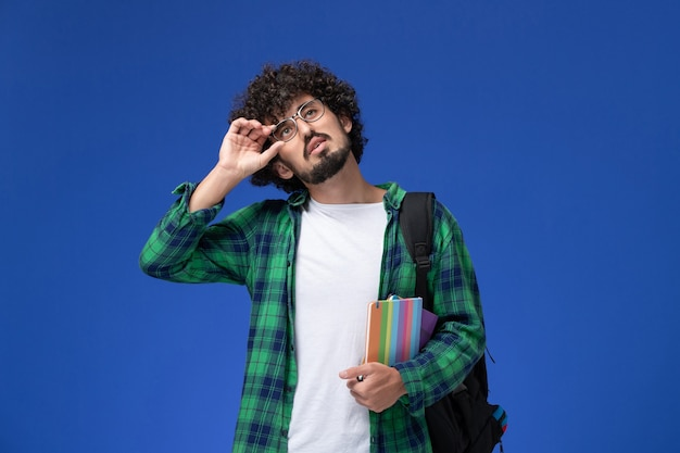 Vooraanzicht van mannelijke student in groen geruit overhemd die zwarte rugzak draagt en voorbeeldenboek op de blauwe muur houdt