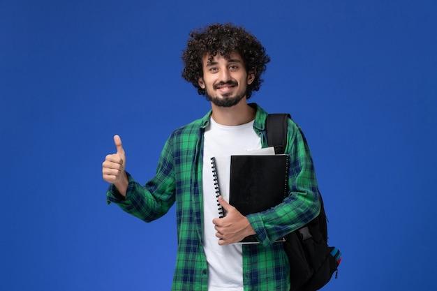 Vooraanzicht van mannelijke student in groen geruit overhemd met zwarte rugzak die voorbeeldenboeken op blauwe muur glimlachen