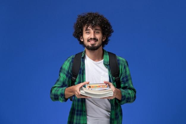Vooraanzicht van mannelijke student in groen geruit overhemd met zwarte rugzak met voorbeeldenboeken en bestanden lachend op de blauwe muur