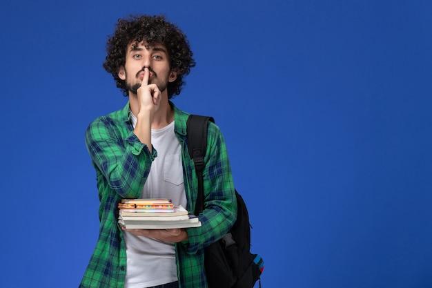 Vooraanzicht van mannelijke student in groen geruit overhemd met zwarte rugzak met voorbeeldenboeken en bestanden op lichtblauwe muur