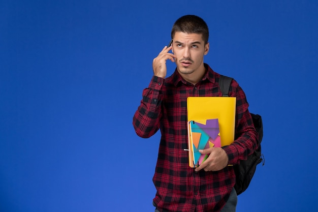 Vooraanzicht van mannelijke student in rood geruit overhemd met de dossiers en voorbeeldenboeken die van de rugzakholding over lichtblauwe muur denken