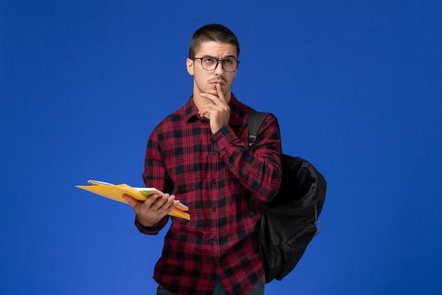 Vooraanzicht van mannelijke student in rood geruit overhemd met de dossiers van de rugzakholding en voorbeeldenboek die op lichtblauwe muur denken