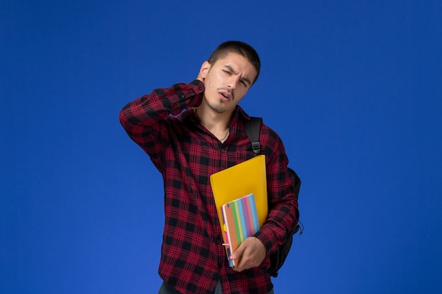 Vooraanzicht van mannelijke student in rood geruit overhemd met de dossiers van de rugzakholding en voorbeeldenboeken die nekpijn op blauwe muur hebben
