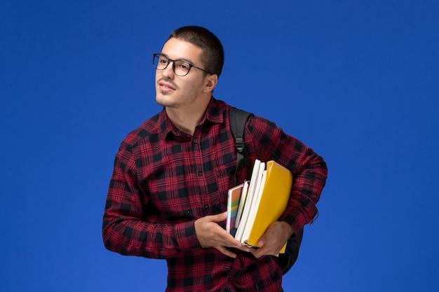 Vooraanzicht van mannelijke student in rood geruit overhemd met de voorbeeldenboeken van de rugzakholding op de lichtblauwe muur