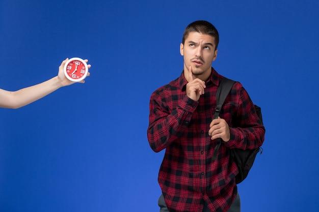 Vooraanzicht van mannelijke student in rood geruit overhemd met rugzak die en op de blauwe muur stellen denken