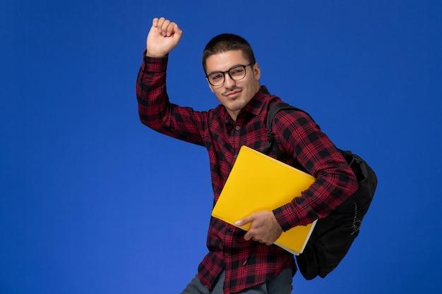 Vooraanzicht van mannelijke student in rood geruit overhemd met rugzak met bestanden op lichtblauwe muur