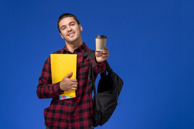 Vooraanzicht van mannelijke student in rood geruit overhemd met rugzak met gele bestanden en koffie op de blauwe muur