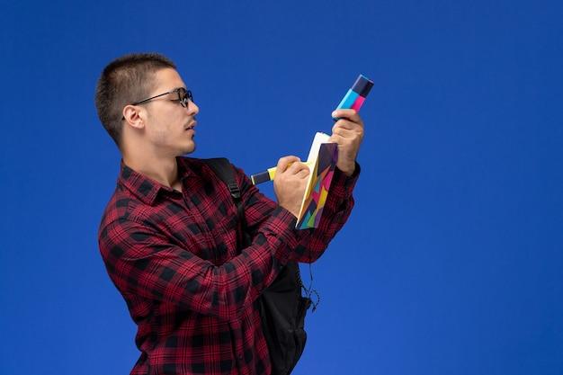 Vooraanzicht van mannelijke student in rood geruit overhemd met rugzak met viltstiften voorbeeldenboek op lichtblauwe muur