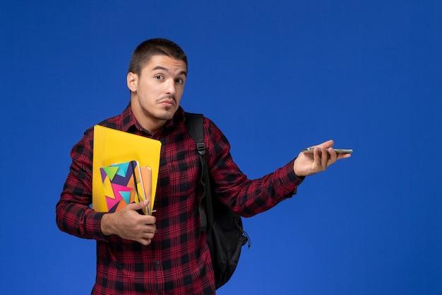 Vooraanzicht van mannelijke student in rood geruit overhemd met voorbeeldenboek van de rugzakholding en dossiers met telefoon op de blauwe muur