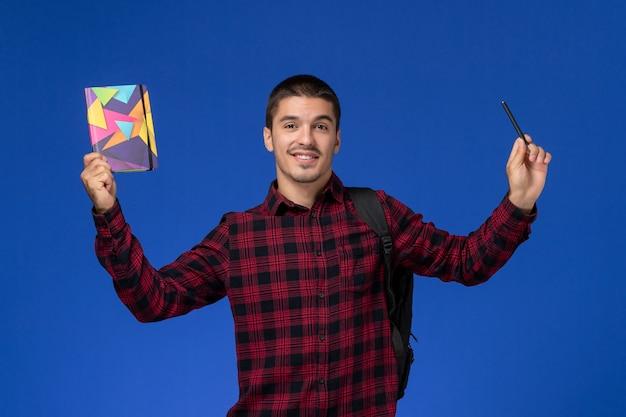 Vooraanzicht van mannelijke student in rood geruit overhemd met voorbeeldenboek van de rugzakholding en pen op lichtblauwe muur
