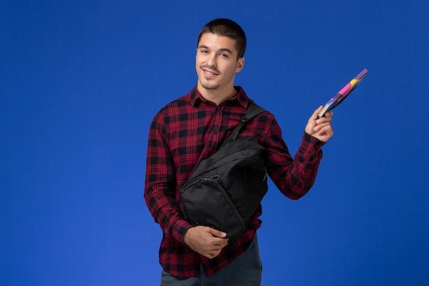 Vooraanzicht van mannelijke student in rood geruit overhemd met voorbeeldenboek van de rugzakholding op de blauwe muur