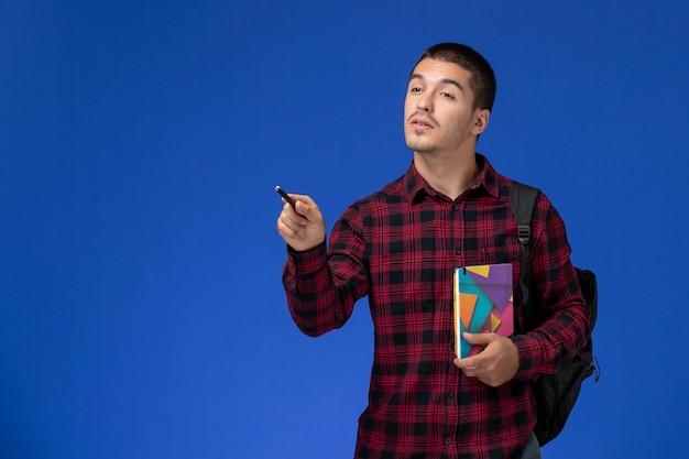 Vooraanzicht van mannelijke student in rood geruit overhemd met voorbeeldenboek van de rugzakholding op de lichtblauwe muur