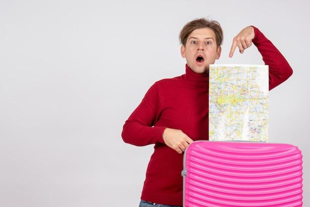 Vooraanzicht van mannelijke toerist met kaart en roze zak op witte muur