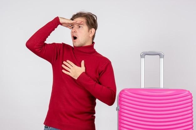Vooraanzicht van mannelijke toerist met roze zak lookign op afstand op witte muur