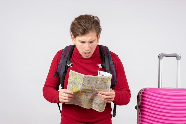 Vooraanzicht van mannelijke toerist met rugzak en kaart op witte muur