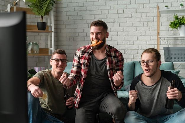 Vooraanzicht van mannelijke vrienden die op tv naar sport kijken en pizza hebben