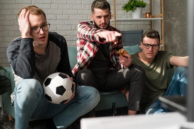 Vooraanzicht van mannelijke vrienden kijken naar sport op tv met pizza en voetbal