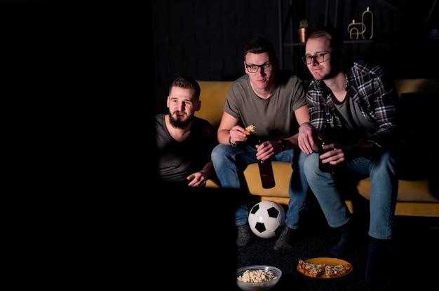 Vooraanzicht van mannelijke vrienden samen kijken naar sport op tv
