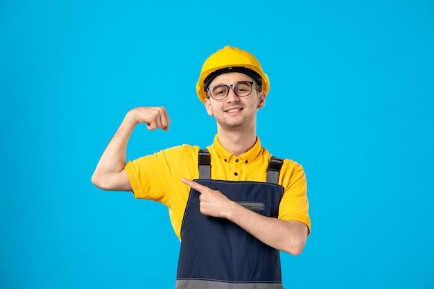 Vooraanzicht van mannelijke werknemer in geel uniform buigen op blauw