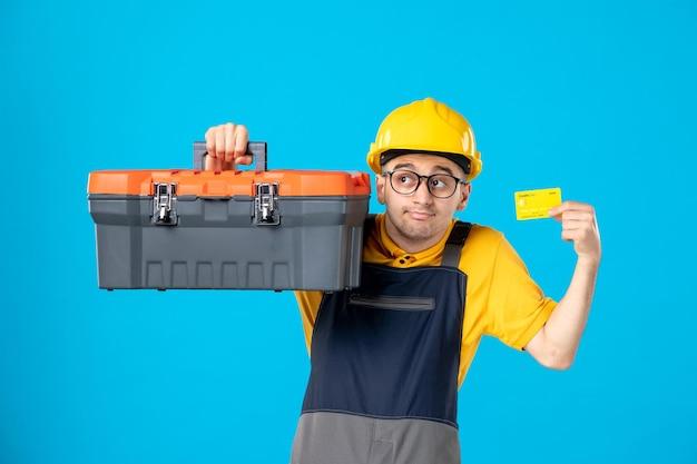 Vooraanzicht van mannelijke werknemer in geel uniform met gereedschapskist op blauw