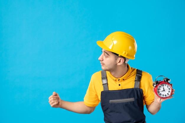 Vooraanzicht van mannelijke werknemer in geel uniform met klokken op blauw