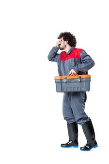 Vooraanzicht van mannelijke werknemer in uniform dragende koffer met gereedschap op witte muur