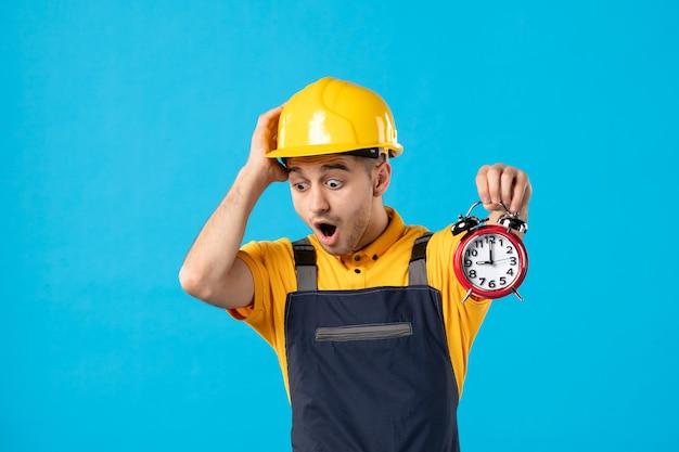 Vooraanzicht van mannelijke werknemer in uniform met klokken die laat op het blauw zijn